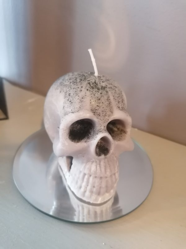Realistic skull candle on a circular mirror platter